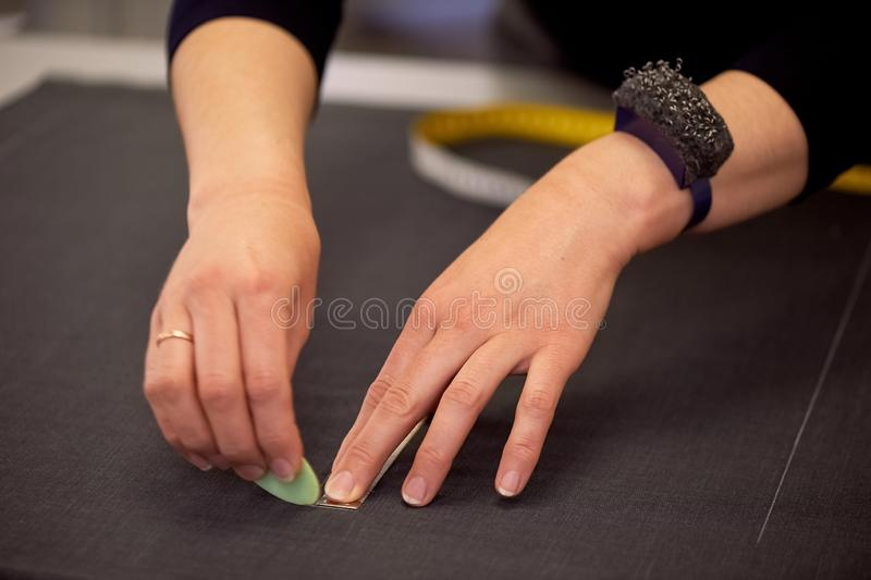 La cucitrice presenta lo schema fine per il taglio del tessuto Adattando nello studio immagini stock libere da diritti