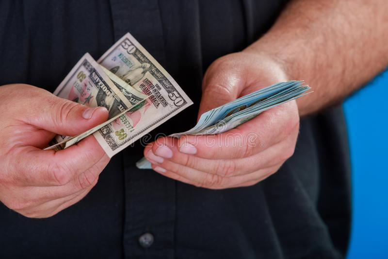 La cuenta del hombre de la moneda de los E.E.U.U. cuenta el dinero Nuevos dólares en las manos cercanas encima de la visión Negoc fotos de archivo