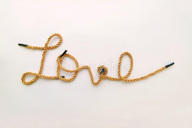 La cuerda de oro del color hace la palabra de la escritura de amor fotografía de archivo libre de regalías