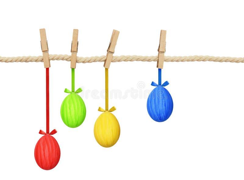 La cuerda del algodón y cuatro pernos con el colgante de Pascua pintaron los huevos imagen de archivo libre de regalías