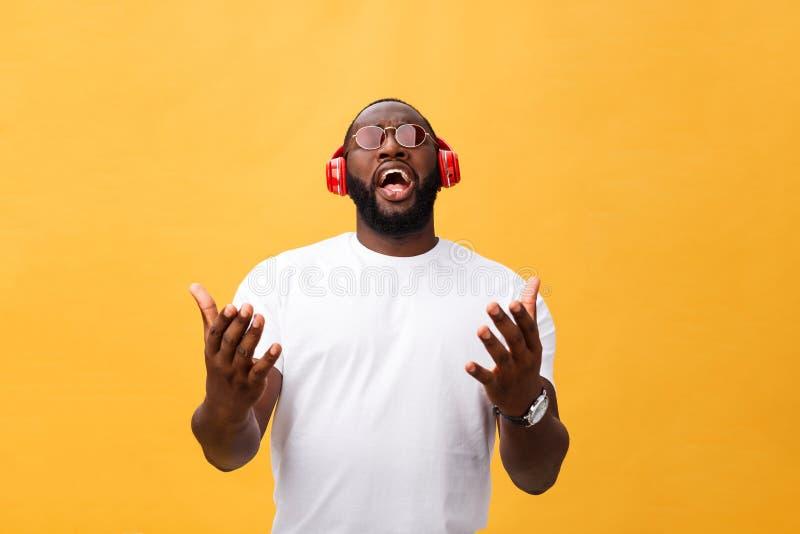 La cuffia d'uso del giovane uomo afroamericano e gode della musica sopra il fondo dell'oro giallo fotografie stock
