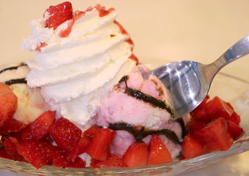 La cuillère de plan rapproché écopant dans la crème glacée de fraise a complété avec les baies fraîches et la crème fouettée photographie stock
