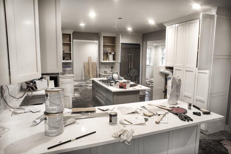 La cuisine à la maison malpropre pendant la retouche avec des portes de coffret s'ouvrent encombré avec des boîtes de peinture, d photos stock