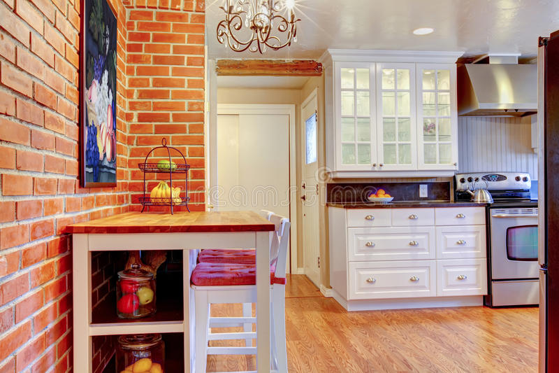 La cuisine blanche avec le mur de briques, le bois dur et inoxydables volent le fourneau. photographie stock