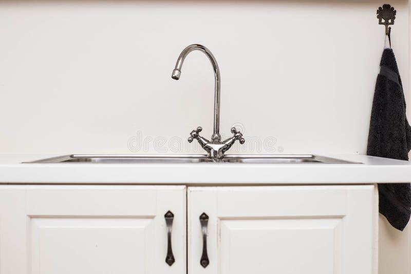 La cuisine blanche moderne avec les accents en bois et le fer descendent la rétro conception en gros plan photographie stock libre de droits