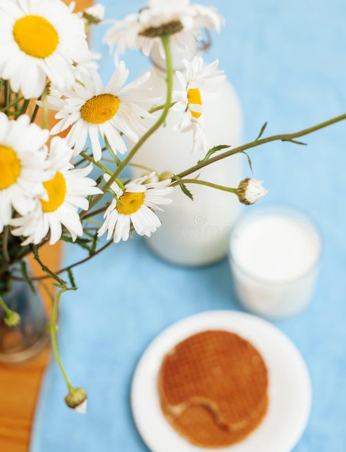 La cuisine en bois simplement élégante avec la bouteille de lait et de verre sur la table, été fleurit la camomille, matin sain d photographie stock libre de droits