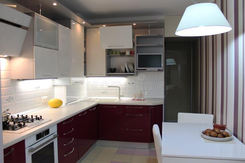 La cuisine moderne brillante avec le dessus blanc et la cerise basent photographie stock