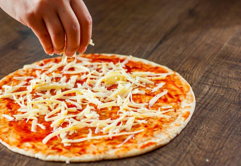 La cuisinière de femme de main avec la cuillère enduit la sauce tomate sur la pâte fabrication de la pizza italienne sur la pizza image libre de droits
