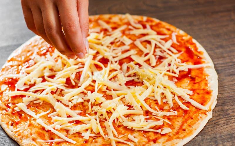 La cuisinière de femme de main avec la cuillère enduit la sauce tomate sur la pâte fabrication de la pizza italienne sur la pizza photos libres de droits