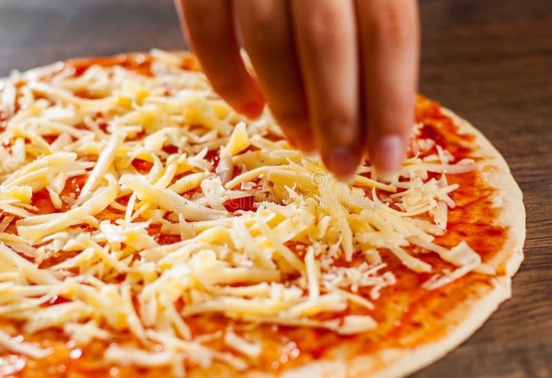 La cuisinière de femme de main avec la cuillère enduit la sauce tomate sur la pâte fabrication de la pizza italienne sur la pizza photo stock