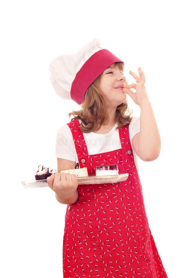 La cuisinière de petite fille avec des gâteaux et la main correcte signent photographie stock