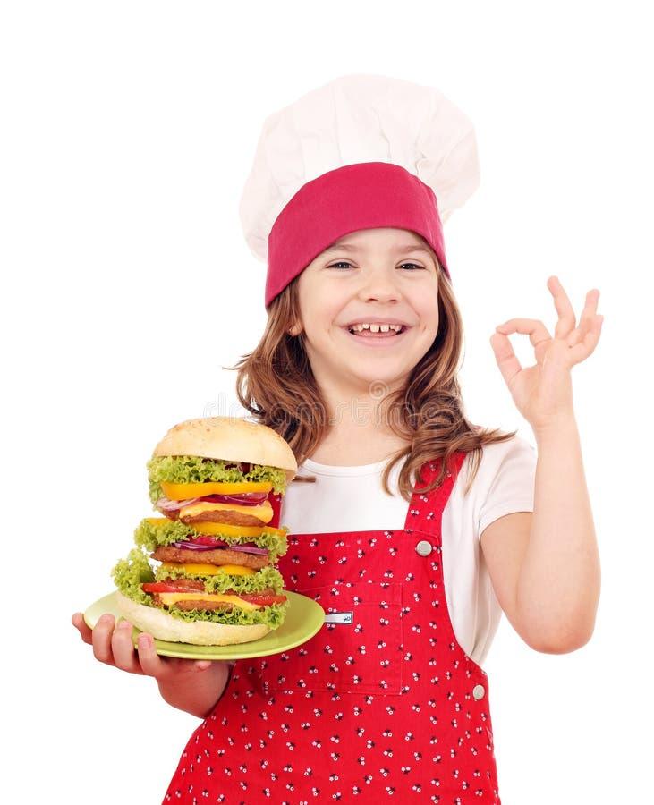 La cuisinière de petite fille avec le grand hamburger et la main correcte signent image libre de droits