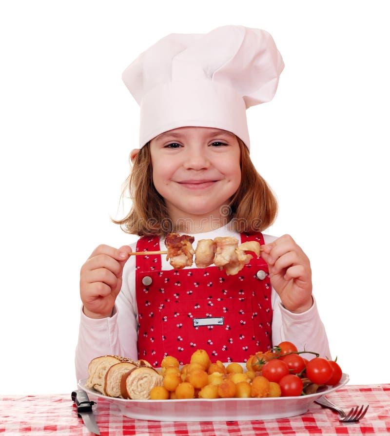 La cuisinière de petite fille mangent de la viande de poulet image stock