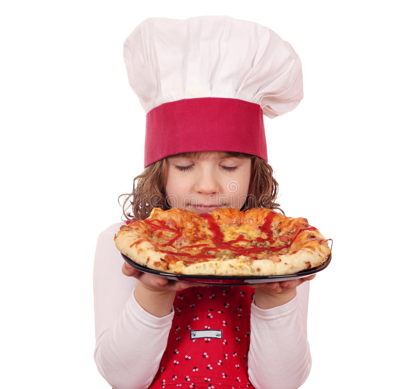 La petite fille sent la pizza photos stock