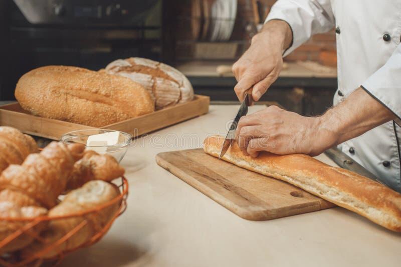 La cuisson de chef de boulangerie font cuire au four dans le professionnel de cuisine photos libres de droits