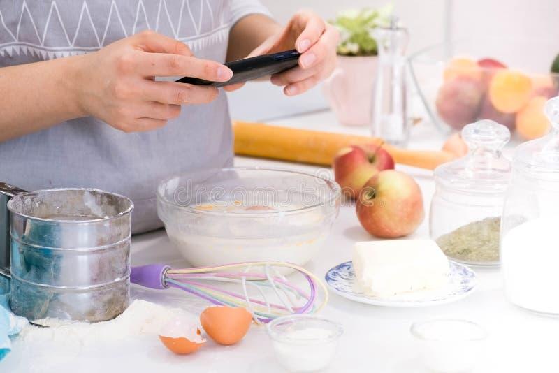 La cuisson du blogger est cuisson à la cuisine dans le jour ensoleillé et fait la photo au smartphone du procédé de cuisson jeune photo libre de droits