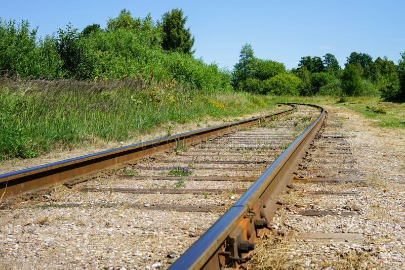La curva della ferrovia avvolge il suo modo attraverso gli alberi e le foreste fotografie stock libere da diritti