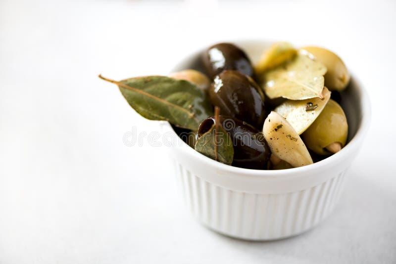La cuvette blanche avec les olives noires et vertes fraîches, ail, baie part sur le fond gris Copiez l'espace image libre de droits