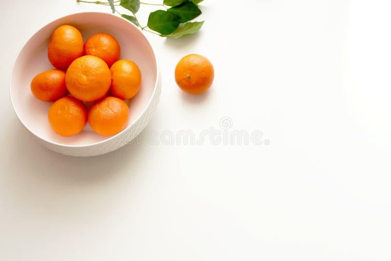 La cuvette blanche de porcelaine a rempli de mandarines fraîches juteuses sur le fond blanc Fruit organique frais de mandarines p image libre de droits