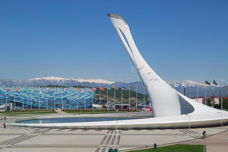 La cuvette de flamme olympique contre le contexte du stade le palais de patinage d'iceberg et les montagnes couronnées de neige s photographie stock