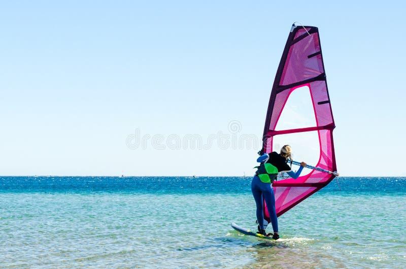 La débutante de planche à voile de jeune fille apprend à monter en mer en Egypte Dahab Sinai du sud image libre de droits