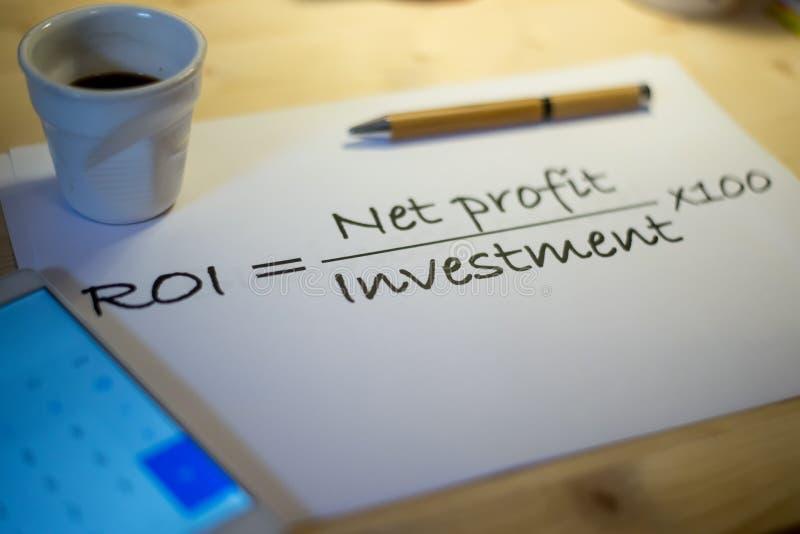 La déclaration de retour sur l'investissement a imprimé sur une feuille de papier blanche au cours d'une réunion d'affaires photographie stock libre de droits