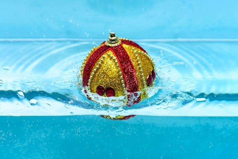 La décoration de fête pour l'arbre de Noël, boule d'or avec le décor de scintillement s'est laissée tomber dans l'eau, fond bleu  photos stock