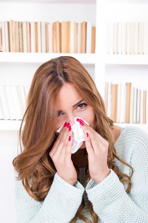 La défectuosité se sentante de belle fille a attrapé des reniflements froids soufflant son nez photo stock