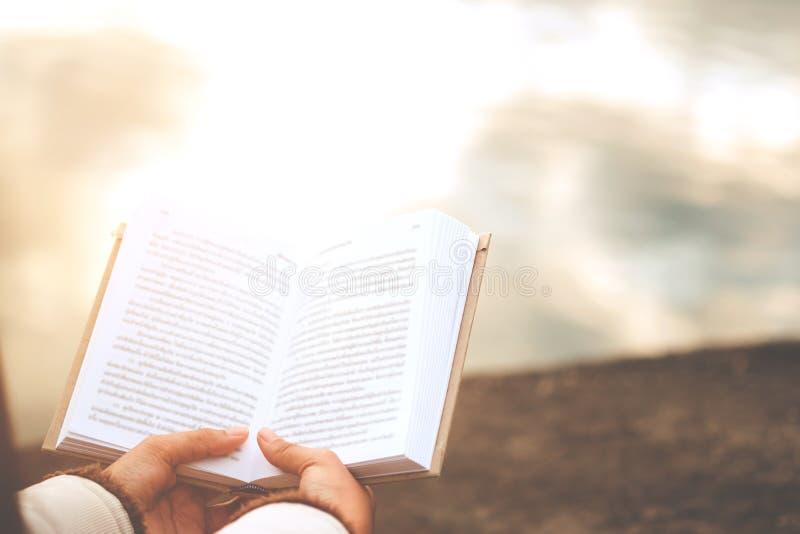 La détente des moments, des jeunes femmes s'ouvrant et livre de lecture apprécie du repos extérieur avec le concept de vacances d photographie stock libre de droits