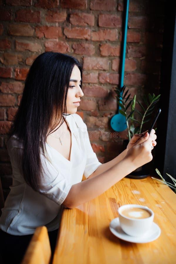 La dactylographie de femme écrivent le message au téléphone intelligent dans un café moderne Image cultivée de la jeune jolie fil photos stock