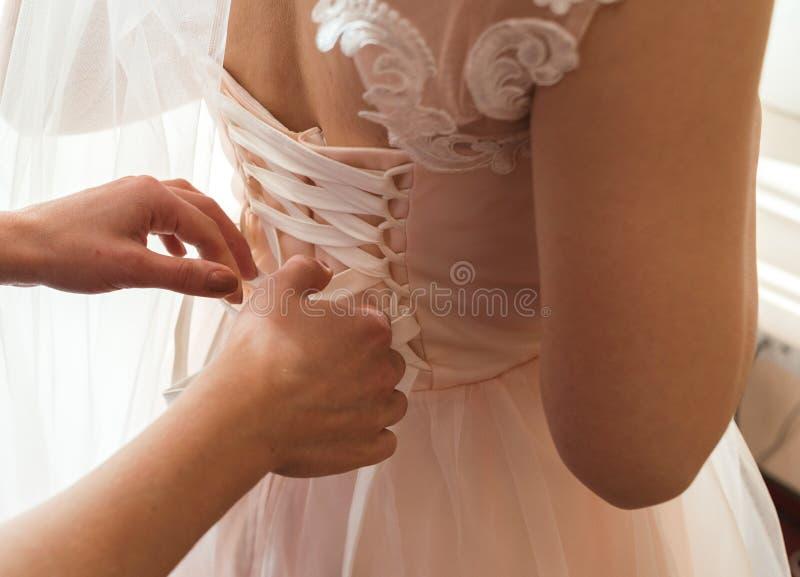 La dama de honor ata el bride& x27; vestido de boda de s en el cuarto fotos de archivo