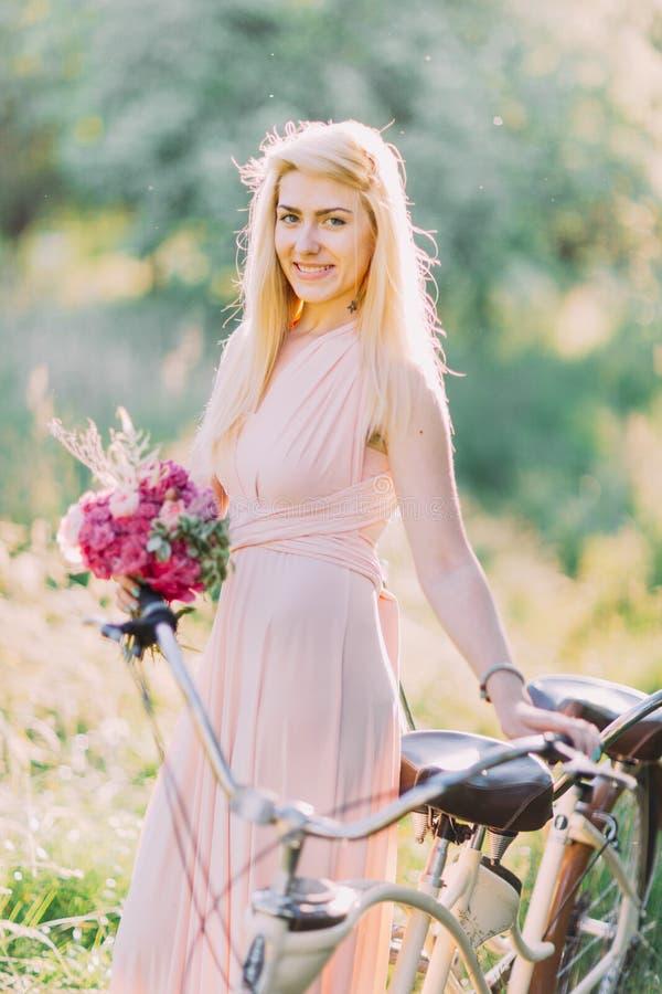 La dama de honor sonriente con el ramo de las flores rosadas se está colocando cerca de la bicicleta en el bosque soleado fotografía de archivo libre de regalías