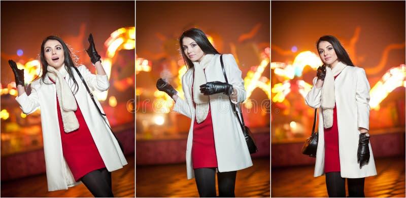 La dame à la mode portant la robe rouge et le manteau blanc extérieurs dans le paysage urbain avec la ville s'allume à l'arrière- image libre de droits