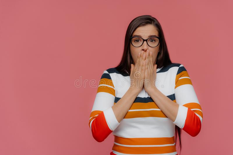 La dame étonnée avec les cheveux foncés couvre la bouche des deux mains, regards dans l'incrédulité à la caméra, porte les lunett photographie stock