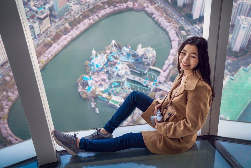 La dame asiatique détendent sur la barre supérieure de toit avec le fond de ville de Séoul images stock