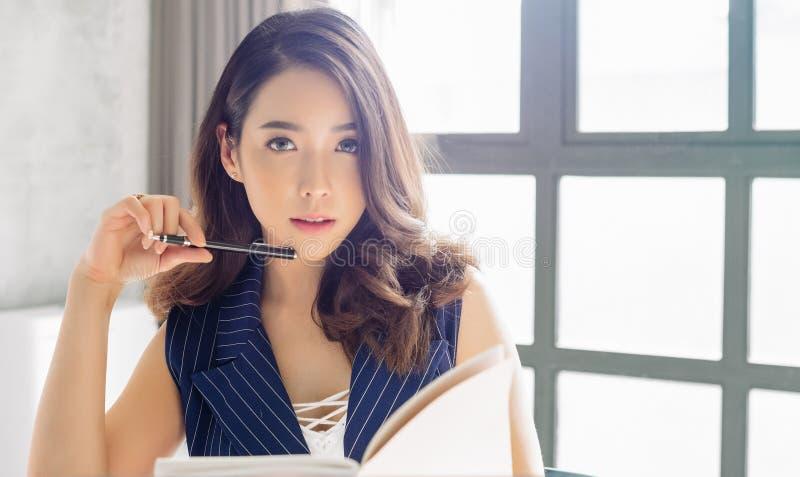 La dame asiatique de belles affaires regarde la caméra tout en travaillant dans le bureau photographie stock