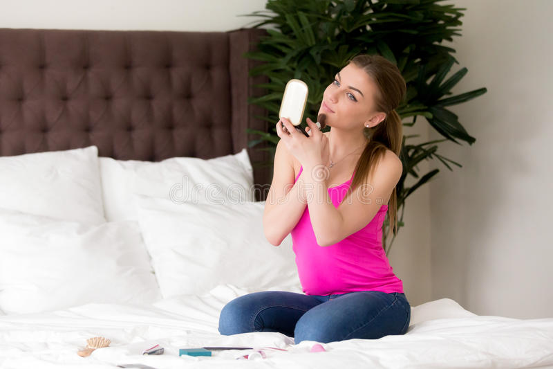 La dame attirante fait le maquillage quotidien de matin à la maison photo libre de droits
