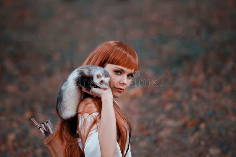 La dame attirante par espièglerie et regarde temptingly dans la caméra, fille avec les cheveux rouges ardents et les coups tient  images libres de droits