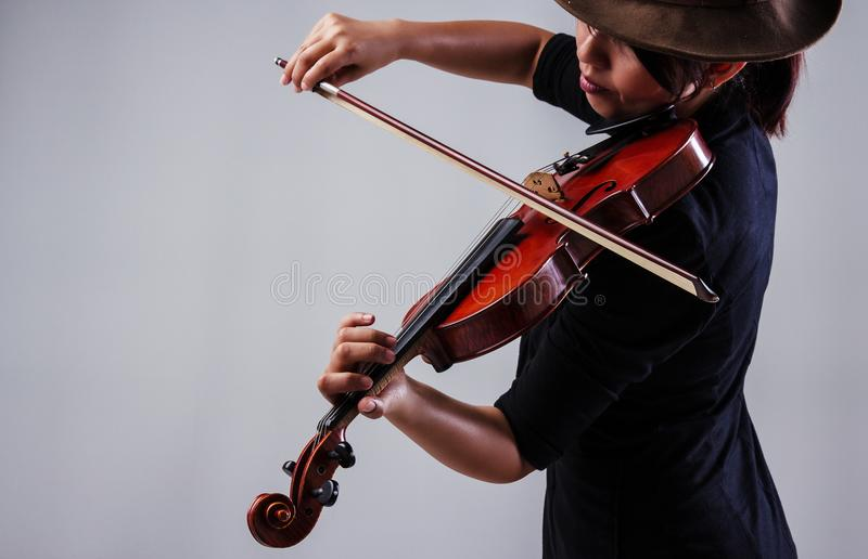 La dame avec le costume noir et le chapeau brun d'usage, jouant le violon image stock
