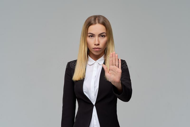 La dame blonde aux cheveux longs attirante sérieuse d'affaires dans le costume formel tient la main devant elle avec la paume dan images stock