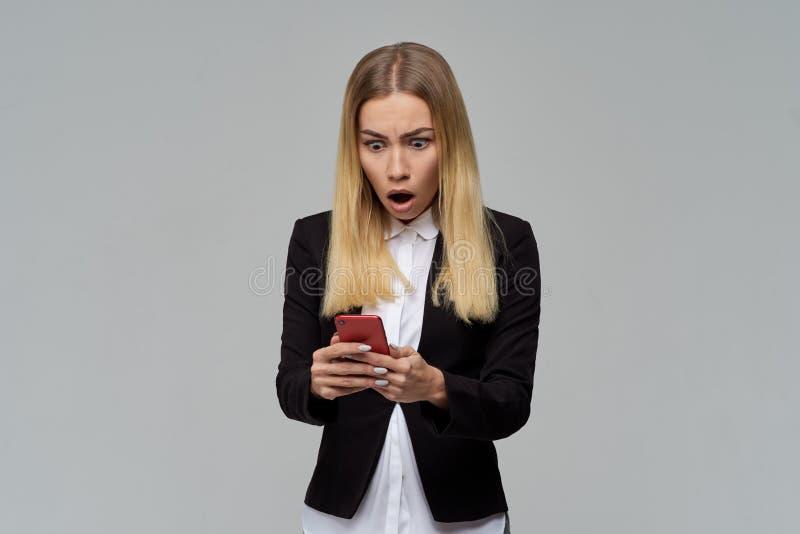 La dame blonde aux cheveux longs d'affaires dans la robe formelle et le chemisier blanc tenant un smartphone et est choquée pour  images stock