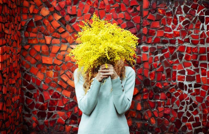 La dame de cru avec un bouquet des fleurs jaunes mimosa, ressort, marchent photo stock