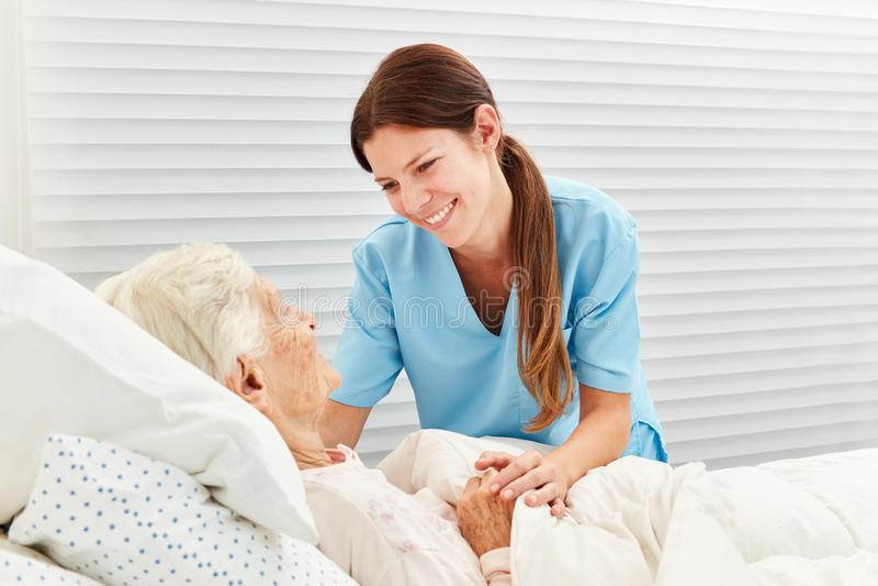 La dame de soins s'occupe d'une femme agée malade photos stock