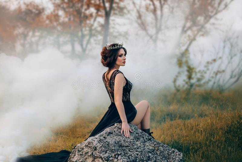 La dame majestueuse, la reine foncée, s'assied sur la pierre découvrant sa jambe La fille de brune dans la couronne gothique E images stock