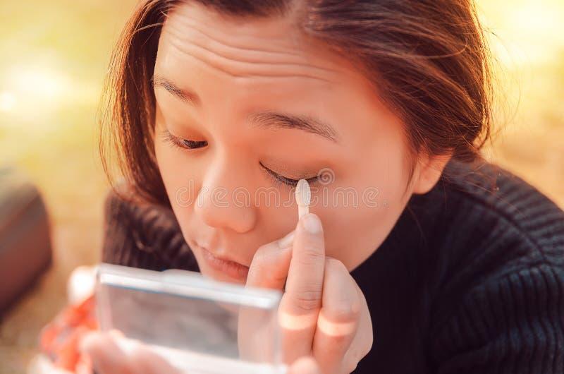 la dame mettant sur elle composent le regard sur un miroir de poche images stock