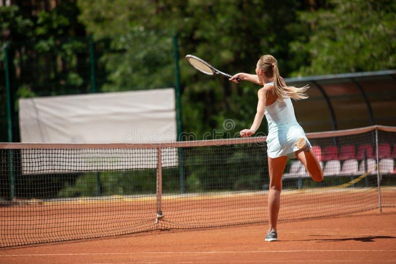 La dame mince joue le tennis sur la cour images stock