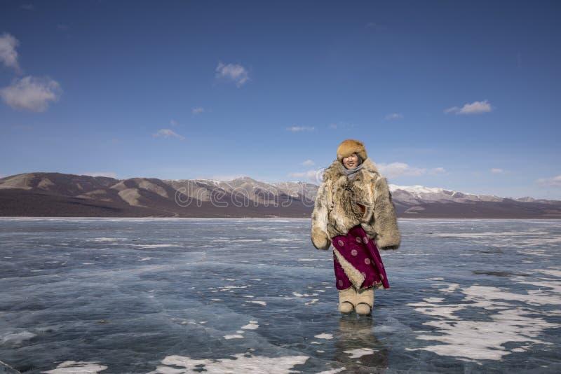 La dame mongole s'est habillée dans l'habillement traditionnel sur un lac congelé photo stock