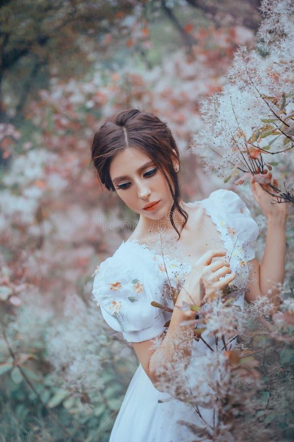 La dame mystérieuse dans une robe légère chère de cru avec des modèles se tient prêt les arbres de floraison, un avec un regard t photographie stock