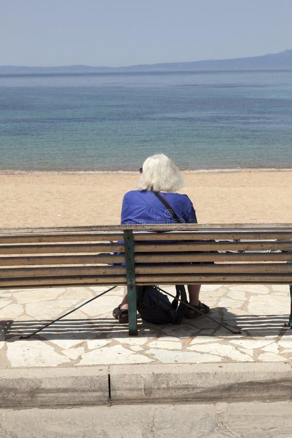 La dame pluse âgé seul s'assied sur le banc et regarde la mer en Grèce images stock
