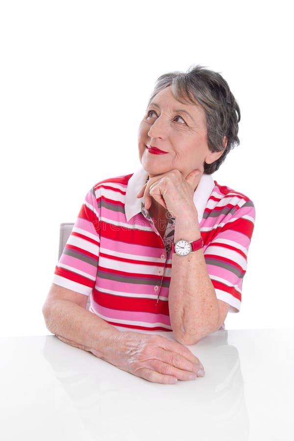 La dame pluse âgé songeuse sourit - une femme plus âgée d'isolement sur le dos de blanc photographie stock